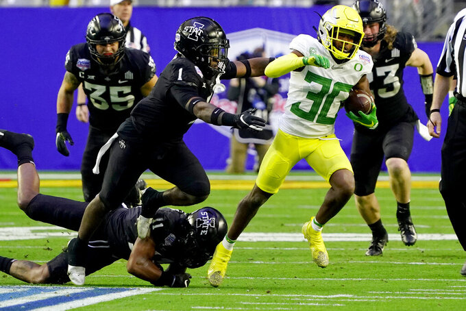 Oregon wide receiver Jaylon Redd (30) eludes the reach of Iowa State defensive back Lawrence White IV (11) and defensive back Isheem Young (1) during the second half of the Fiesta Bowl NCAA college football game, Saturday, Jan. 2, 2021, in Glendale, Ariz. (AP Photo/Rick Scuteri)