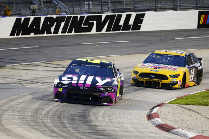 Jimmie Johnson (48) leads Clint Bowyer (14) through a turn during a NASCAR Cup Series auto race Wednesday, June 10, 2020, in Martinsville, Va. (AP Photo/Steve Helber)