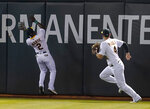 Oakland Athletics center fielder Starling Marte (2) cannot catch a double hit by Seattle Mariners' Mitch Haniger next to right fielder Chad Pinder (4) during the fifth inning of a baseball game in Oakland, Calif., Monday, Sept. 20, 2021. (AP Photo/Jeff Chiu)
