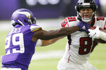 Atlanta Falcons tight end Austin Hooper (81) tries to break a tackle by Minnesota Vikings cornerback Xavier Rhodes during the first half of an NFL football game Sunday, Sept. 8, 2019, in Minneapolis. (AP Photo/Jim Mone)