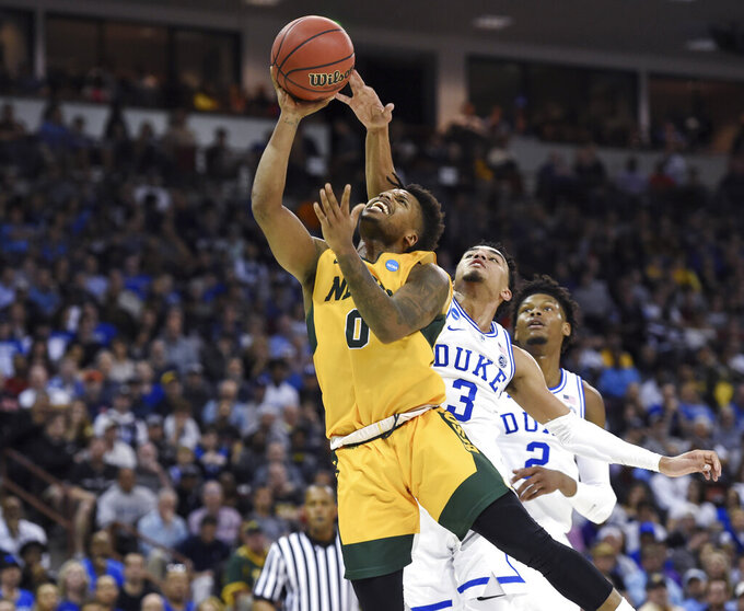 North Dakota State's Vinnie Shahid (0) drives to the basket while defended by Duke's Tre Jones (3) and Cam Reddish (2) during the first half of a first-round game in the NCAA men's college basketball tournament Friday, March 22, 2019, in Columbia, S.C. (AP Photo/Richard Shiro)
