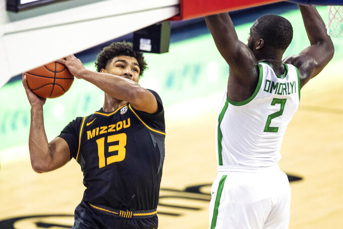 Missouri's Mark Smith (13) looks to pass around Oregon's s Eugene Omoruyi during an NCAA college basketball game, Wednesday, Dec. 2, 2020 in Omaha, Neb. (Chris Machian/Omaha World-Herald via AP)