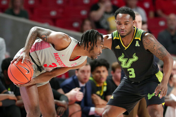 Houston guard DeJon Jarreau (3) looks for a way around South Florida guard Laquincy Rideau (3) during the first half of an NCAA college basketball game Sunday, Jan. 26, 2020, in Houston. (AP Photo/Michael Wyke)