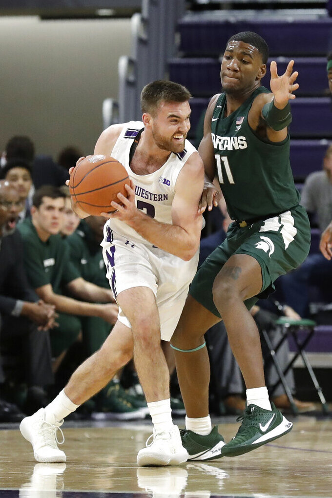 Michigan State forward Aaron Henry, right, guards Northwestern guard Pat Spencer during the first half of an NCAA college basketball game Wednesday, Dec. 18, 2019, in Evanston, Ill. (AP Photo/Nam Y. Huh)