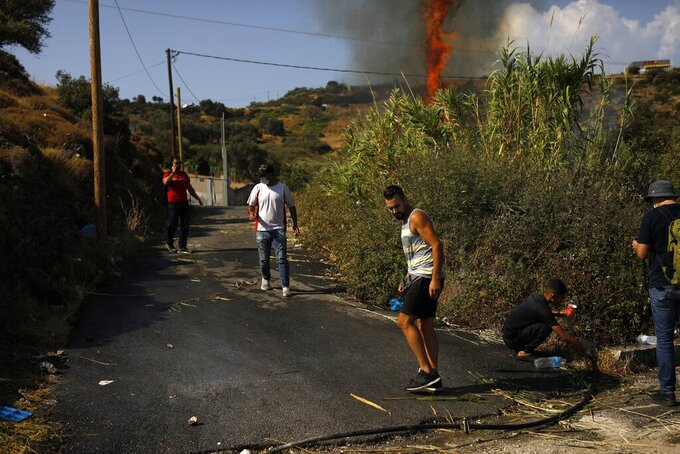 Migrants try to extinguish a small fire in a field near Mytilene town, on the northeastern island of Lesbos, Greece, Saturday, Sept. 12, 2020. Thousands of asylum-seekers spent a fourth night sleeping in the open on the Greek island of Lesbos, after successive fires destroyed the notoriously overcrowded Moria camp during a coronavirus lockdown. (AP Photo/Petros Giannakouris)