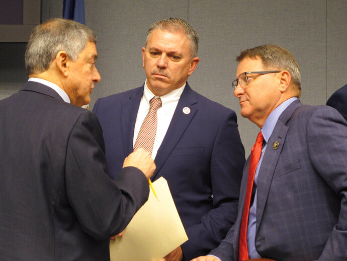 FILE - In a Feb. 7, 2020 file photo, Commissioner of Administration Jay Dardenne, the governor's chief budget adviser, left; House Speaker Clay Schexnayder, R-Gonzales, center; and Senate President Page Cortez, R-Lafayette, speak ahead of a meeting of Louisiana's income forecasting panel in Baton Rouge. Louisiana's income forecasting panel planned to quantify on Monday, May 11, 2020 just how deeply the coronavirus outbreak has hurt the state's economy as officials begin to put together next year's budget.  (AP Photo/Melinda Deslatte, File)
