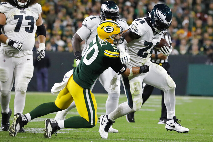 Philadelphia Eagles running back Jordan Howard runs after making a catch and breaks the tackle of Green Bay Packers inside linebacker Blake Martinez during the second half of an NFL football game Thursday, Sept. 26, 2019, in Green Bay, Wis. (AP Photo/Jeffrey Phelps)
