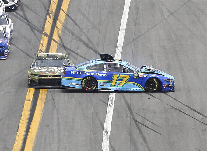 Ricky Stenhouse Jr., right, gets turned sideways as Kurt Busch, left, makes contact as the cars come out of turn 4 during the NASCAR Cup Series auto race at Daytona International Speedway, Sunday, July 7, 2019, in Daytona Beach, Fla. Both drivers were able to continue with the race. (AP Photo/David Graham)