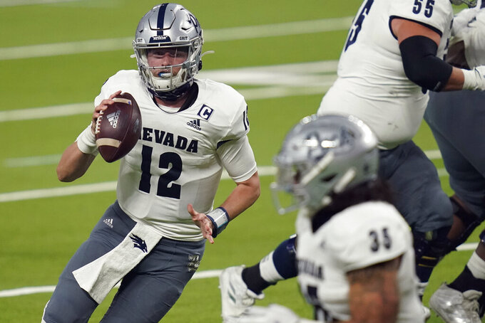 Nevada quarterback Carson Strong (12) looks for a receiver during the first half of the team's NCAA college football game against UNLV on Saturday, Oct. 31, 2020, in Las Vegas. (AP Photo/John Locher)