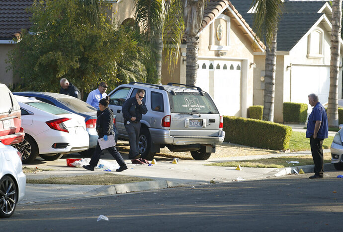 Fresno police investigators work the driveway where a shooting took place at a house party which involved multiple fatalities and injuries in Fresno, Calif., Monday, Nov. 18, 2019. (AP Photo/Gary Kazanjian)