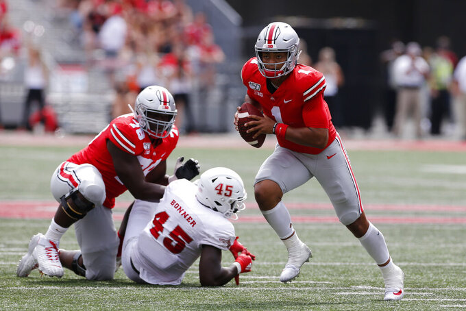 Ohio State quarterback Justin Fields, right, runs up field as teammate Nicholas Petit-Frere, left, blocks Florida Atlantic defensive end Tim Bonner during the second half of an NCAA college football game Saturday, Aug. 31, 2019, in Columbus, Ohio. Ohio State beat Florida Atlantic 45-21. (AP Photo/Jay LaPrete)
