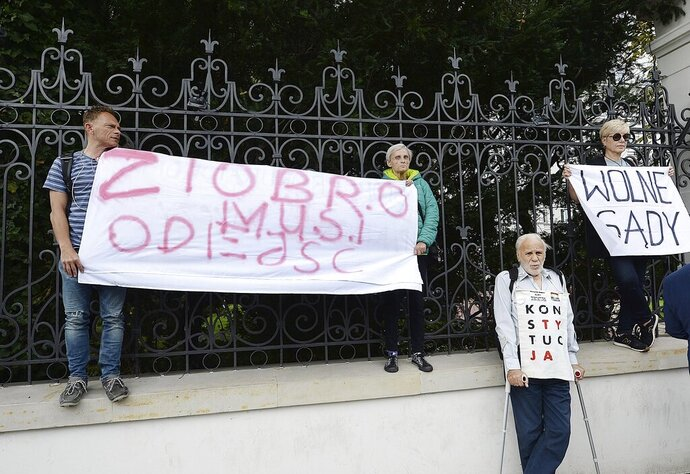 Protesters with banners calling on Justice Minister Zbigniew Ziobro to quit over allegations that his deputy encouraged an online hate campaign against defiant judges in Warsaw, Poland, Wednesday, Aug. 21, 2019. The deputy, Lukasz Piebiak, has resigned over the allegations but said they were libel that he will take to court. The banner reads