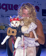 In this Wednesday, Oct. 23, 2019, photo provided by the Florida Keys News Bureau, Diana Benton shows off her two cats dressed as country superstars Willie Nelson and Dolly Parton during the Fantasy Fest Pet Masquerade in Key West, Fla. The event was one of many activities during Key West's 10-day costuming and masking festival that continues through Sunday, Oct. 27. (Rob O'Neal/Florida Keys News Bureau via AP)
