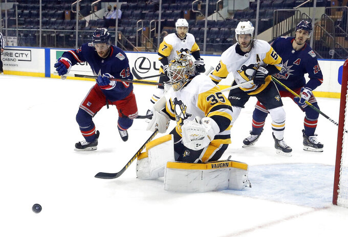 Pittsburgh Penguins' Tristan Jarry (35) sticks aside a  shot as New York Rangers' Brendan Smith (42) looks for the rebound during the first period of an NHL hockey game Thursday, April 8, 2021, in New York. (Bruce Bennett/Pool Photo via AP)