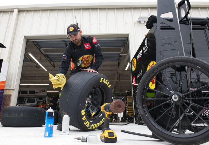 Tommy DiBlasi, a tire specialist for Martin Truex Jr., prepares tires for the Drydene 400 - Monster Energy NASCAR Cup Series playoff auto race, Sunday, Oct. 6, 2019, at Dover International Speedway in Dover, Del. (AP Photo/Jason Minto)