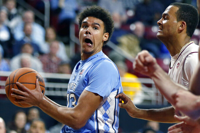 North Carolina's Cameron Johnson (13) drives past Boston College's Steffon Mitchell, right, during the second half of an NCAA college basketball game in Boston, Tuesday, March 5, 2019. (AP Photo/Michael Dwyer)