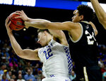 Kentucky's Reid Travis, left, grabs a rebound away from Wofford's Tray Hollowell during the first half of a second-round game in the NCAA men's college basketball tournament in Jacksonville, Fla., Saturday, March 23, 2019. (AP Photo/Stephen B. Morton)