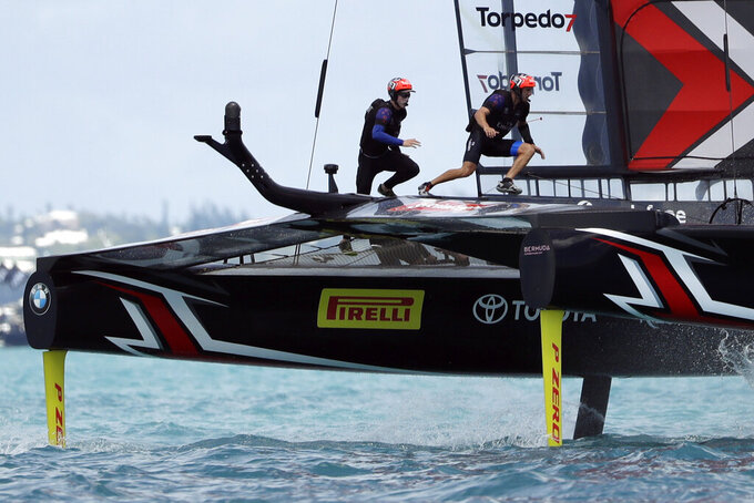 FILE - In this June 26, 2017, file photo, Emirates Team New Zealand helmsman Peter Burling, left, and teammate Blair Tuke cross the boat during the ninth race in America's Cup sailing competition against Oracle Team USA in Hamilton, Bermuda. As they hit what could be the prime of their careers, Burling, 30, and Tuke, 31, are thinking about more than just their next victory. Sure, they're focusing in on trying to win another gold medal in the high-performance 49er skiff in the Tokyo Olympics starting later this month. They also realize that as the victories pile up, they're in a unique position to speak out about protecting the planet's oceans. (AP Photo/Gregory Bull, File)