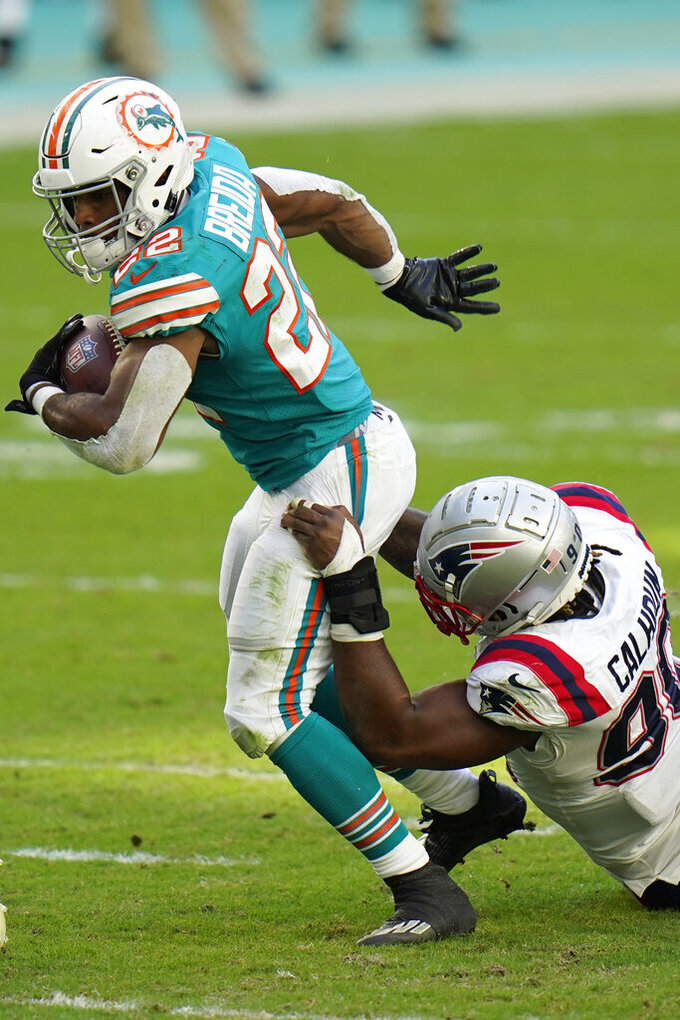 New England Patriots linebacker Shilique Calhoun (90) brings down Miami Dolphins running back Matt Breida (22) during the second half of an NFL football game, Sunday, Dec. 20, 2020, in Miami Gardens, Fla. (AP Photo/Chris O'Meara)