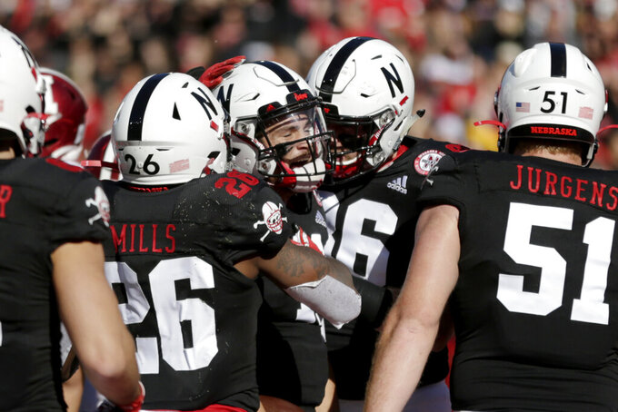 Nebraska quarterback Noah Vedral, center, is surrounded by teammates after scoring his second touchdown against Indiana during the first half of an NCAA college football game in Lincoln, Neb., Saturday, Oct. 26, 2019. (AP Photo/Nati Harnik)