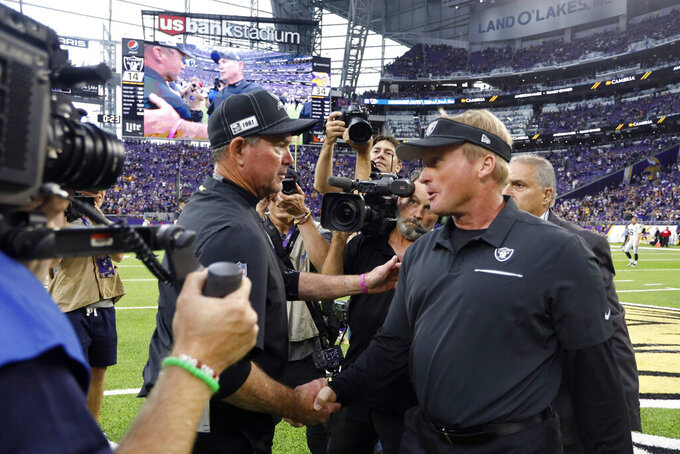 Minnesota Vikings head coach Mike Zimmer, left, talks with Oakland Raiders head coach Jon Gruden after an NFL football game, Sunday, Sept. 22, 2019, in Minneapolis. The Vikings won 34-14. (AP Photo/Bruce Kluckhohn)