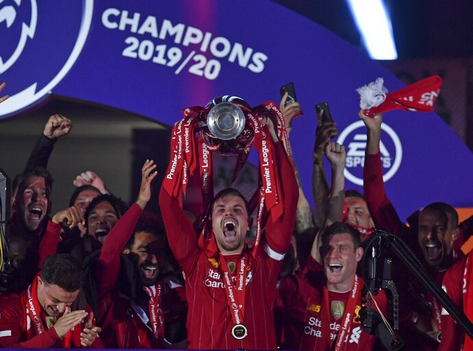 Liverpool's Jordan Henderson holds the English Premier League trophy aloft after it was presented following the Premier League soccer match between Liverpool and Chelsea at Anfield stadium in Liverpool, England, Wednesday, July 22, 2020. (Paul Ellis, Pool via AP)