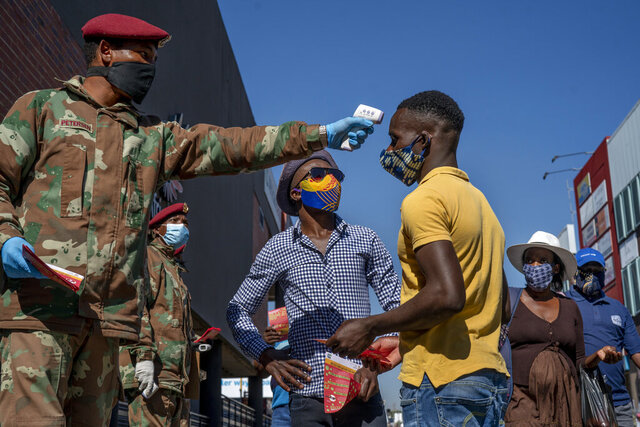 South African National Defense Forces check people's temperature near the Pan Africa taxi rank in Johannesburg's Alexandra township, Wednesday May 20, 2020. South Africa has the continent's highest number of confirmed cases and has eased its restrictions to allow an estimated 1.6 million people to return to work in selected mines, factories and businesses. (AP Photo/Jerome Delay)