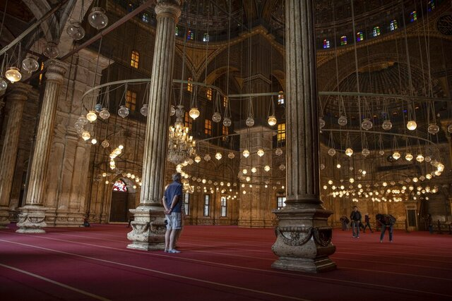 FILE - In this March 18, 2020, file photo, an American tourist looks at the great Mosque of Muhammad Ali Pasha at the Citadel complex, in Cairo, Egypt. Muslims will be grappling during the upcoming Islamic holy month of Ramadan with how to observe familiar rituals in a time of unfamiliarity after the coronavirus has disrupted Islamic worship. (AP Photo/Nariman El-Mofty, File)