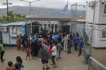 FILE - In this Wednesday, Sept. 25, 2019, file photo, refugees and migrants wait outside the information office at a refugee and migrant camp at the Greek island of Samos. Greece's government says on Monday, Feb. 10, 2020 it is planning to use emergency legal powers to create detention centers for migrants on five Greece islands to try and speed up deportations back to Turkey. (AP Photo/ Petros Giannakouris, File)