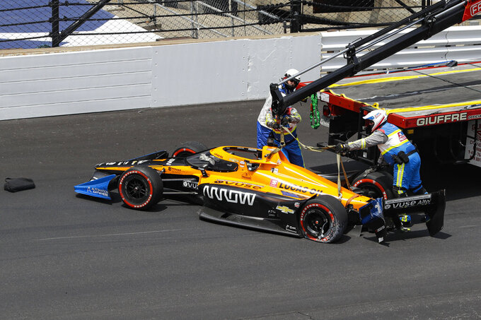 The car driven by race driver Oliver Askew is removed from the track after making contact with the wall during the IndyCar auto race at Indianapolis Motor Speedway in Indianapolis, Saturday, July 4, 2020. (AP Photo/Darron Cummings)