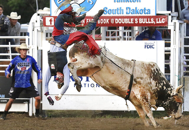 FILE - In this Aug. 18, 2018, file photo, Jordan Allen of Buffalo, Mo., is thrown from this bull during competition at the Extreme Bull Riding Tour stop in Yankton, S.D. Professional Bull Riders has announced a new series of competition that will culminate in South Dakota on July 10-12 with live crowds. Event organizers said they will provide face coverings to fans, space seats four to six feet apart and control the flow of people in and out of the arena to accommodate social distancing. (Kelly Hertz/Yankton Press & Dakotan via AP, File)