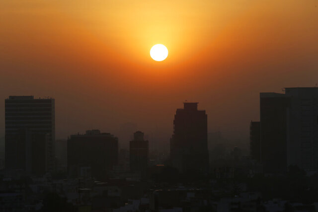 FILE - In this Thursday, Feb. 20, 2020 file photo, the sun rises amid smog during the dry season in Mexico City. Five years after a historic climate deal in Paris, world leaders are again meeting to increase their efforts to fight global warming. (AP Photo/Marco Ugarte)