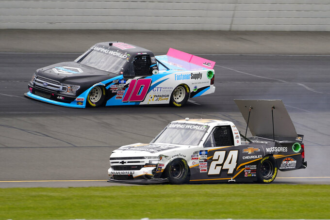 Jennifer Cobb (10) passes the damaged truck of Jack Wood (24) after a first lap shunt during a NASCAR Truck Series auto race at Pocono Raceway, Saturday, June 26, 2021, in Long Pond, Pa. (AP Photo/Matt Slocum)