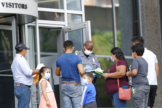 A security officer, center, meets with people outside the federal building to give them a form to return for immigration check-ins at a later date, Monday, July 13, 2020, in Baltimore. Some immigration courts across the country have reopened after closing because of the coronavirus pandemic. (AP Photo/Julio Cortez)