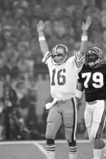 FILE - In this Jan. 24, 1982, file photo, San Francisco 49ers quarterback Joe Montana signals a touchdown after throwing a pass to running back Earl Cooper in the second quarter of Super Bowl XVI against the Cincinnati Bengals in Pontiac, Mich., as Bengals' Ross Browner (79) looks on. (AP Photo/File)