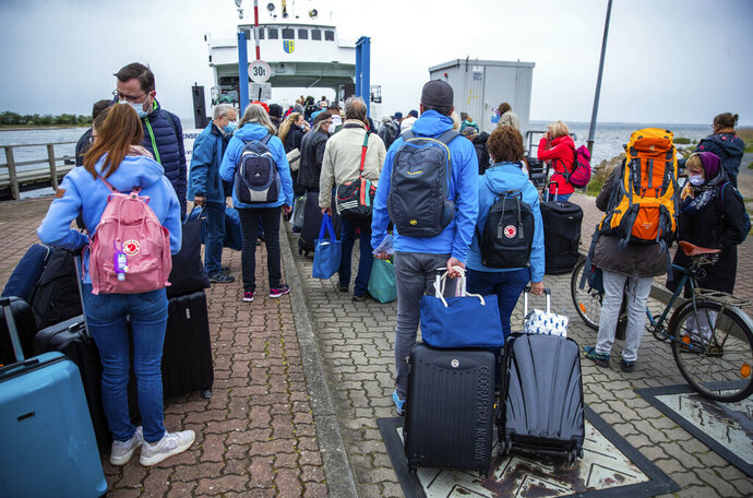 25 May 2020, Mecklenburg-Western Pomerania, Schaprode: Tourists with backpacks and suitcases wait on a pier for transport with a ferry to the Baltic island Hiddensee in Schaprode, Germany, Monday May 25, 2020. In German state Mecklenburg-Western Pomerania, after the travel ban due to the coronavirus protection measures, holidaymakers from other federal states are now allowed to travel to the island. ( Jens Buettner/dpa via AP)