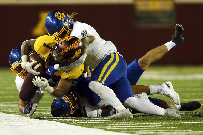 Minnesota running back Rodney Smith (1) is tackled by South Dakota State safety Jarek Berg (14), defensive end Austin Smenda (34) and linebacker Seven Wilson (7) during an NCAA college football game Thursday, Aug. 29, 2019, in Minneapolis. (AP Photo/Stacy Bengs)