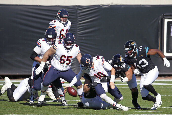 Chicago Bears quarterback Mitchell Trubisky (10) recovers his own fumble ahead of Jacksonville Jaguars linebacker Joe Giles-Harris (43) during the first half of an NFL football game, Sunday, Dec. 27, 2020, in Jacksonville, Fla. (AP Photo/Stephen B. Morton)