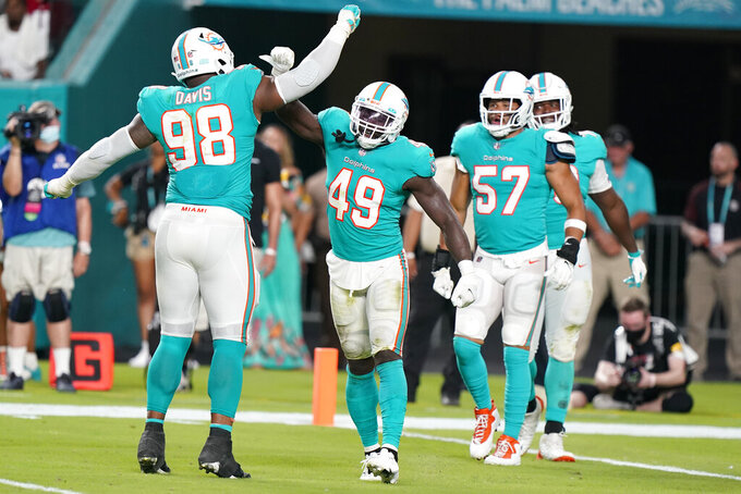 Miami Dolphins linebacker Sam Eguavoen (49) is congratulated by defensive tackle Raekwon Davis (98) after Eguavoen sacked Atlanta Falcons quarterback Feleipe Franks (15) in the endzone for a safety, during the second half of a NFL preseason football game, Saturday, Aug. 21, 2021, in Miami Gardens, Fla. (AP Photo/Wilfredo Lee)