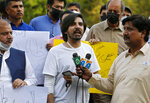 FILE - In this Friday, May 28, 2021, file photo, Pakistani journalist Asad Ali Toor, center, who was beaten and injured by three unidentified men in an attack, speaks during a demonstration called by journalists union to condemn the attack on journalists, in Islamabad, Pakistan. Toor said Tuesday, June 1, 2021, he had been summoned by authorities to answer allegations he defamed a key national institution, a term often used for the military. (AP Photo/Anjum Naveed, File)