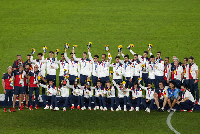 Played of Spain pose after winning the silver medal after the men's soccer final match at the 2020 Summer Olympics, Sunday, Aug. 8, 2021, in Yokohama, Japan. (AP Photo/Martin Mejia)