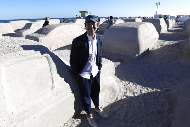 Artist Leandro Erlich, of Argentina, poses with his work featuring cars sculpted in sand stuck in a traffic jam, titled Order of Importance, displayed as part of Miami Art Week, Tuesday, Dec. 3, 2019, in Miami Beach, Fla. Erlich was commissioned by the city of Miami Beach to create the work, which was unveiled during Art Basel Miami. (AP Photo/Lynne Sladky)