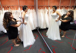 In this Friday, June 21, 2019, photo Ann Campeau, left, owner of Strut Bridal, fits a new dress on inventory manager Stefanie Zuniga at her shop in Tempe, Ariz. Cut-rate prices on websites that sell wedding dresses direct from China put pressure on Campeau, who owns four bridal shops in California and Arizona. She has had customers come in after seeing low-end gowns online and expecting to get a dress at a similar price. (AP Photo/Matt York)