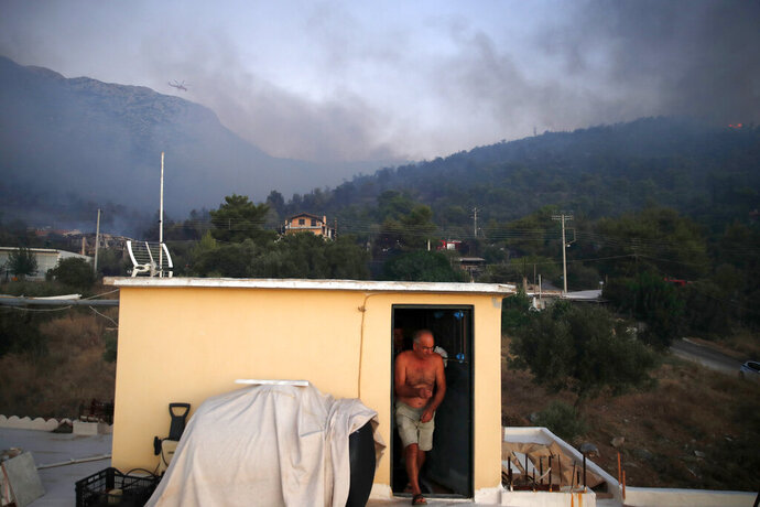A local resident walks out of the rooftop of his house during a wildfire in Peania, eastern Athens, Monday, Aug. 12, 2019. A big fire broke out in the Athens suburb of Peania east of the city, and authorities ordered the evacuation of nearby houses. (AP Photo/Thanassis Stavrakis)