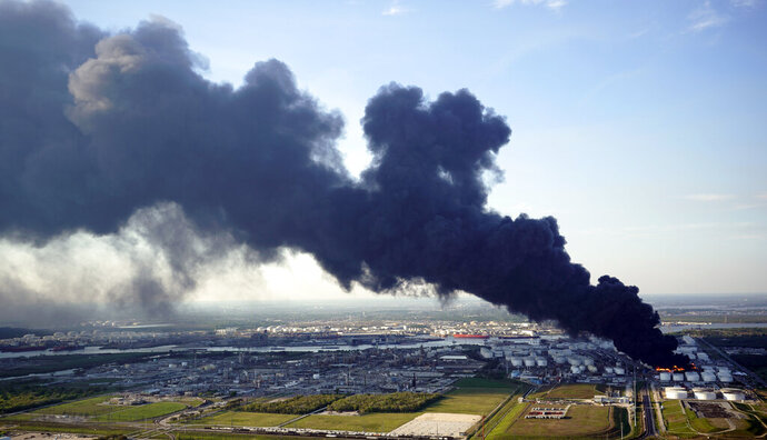 FILE - In this March 18, 2019 file photo, a plume of smoke rises from a petrochemical fire at the Intercontinental Terminals Company in Deer Park, Texas. It's been four months since the explosion and fire at a Houston-area petrochemical storage site and experts are still working to dispose of millions of gallons of waste and contaminated water. The Houston Chronicle reports Intercontinental Terminals Company must comply with a 31-page management plan that details how waste is sampled and identified, stored and finally disposed of. More than 21 million gallons of water mixed with product and firefighting foam were collected from the tank farm and Houston Ship Channel following the March 17 accident that triggered air quality warnings. (AP Photo/David J. Phillip, File)