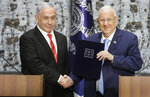 FILE - In this  Sept. 25, 2109 file photo, Israeli President Reuven Rivlin, right, shakes hands with Israeli Prime Minister Benjamin Netanyahu in Jerusalem. Rivlin said Monday, Oct. 21, 2019, that Prime Minister Benjamin Netanyahu has ended his quest to form a new coalition government -- a step that pushes the country into new political uncertainty. Netanyahu fell short of securing a 61-seat parliamentary majority in last month's national election. (AP Photo/Sebastian Scheiner, File)