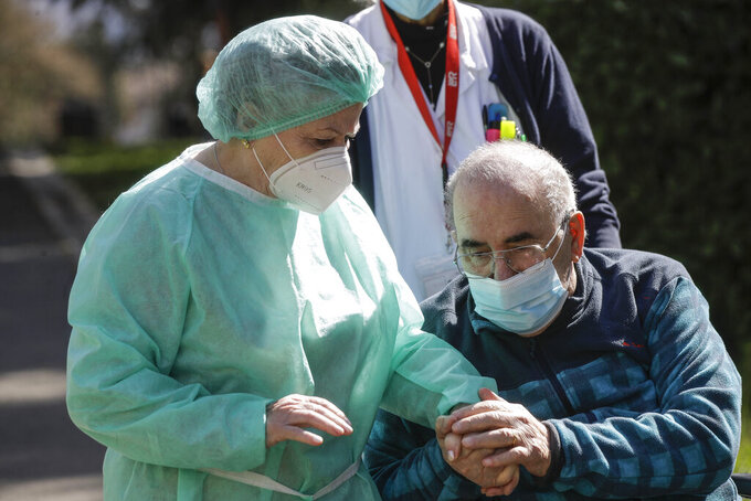 Palmiro Tami, 82, holds hand with his wife Franca Persico as the have a walk in the garden of the Fondazione Martino Zanchi nursing home, after receiving the second shot of Moderna COVID-19 Vaccine, in Alzano Lombardo, northern Italy, Monday, March 22, 2021. Italy's nursing homes have been declared an initial success in an otherwise lagging vaccine campaign. At a nursing home near Bergamo, one 82-year-old resident received his second jab, and a surprise visit from his 77-year-old wife. Their last hug had been through plastic on his birthday, in February. (AP Photo/Luca Bruno)