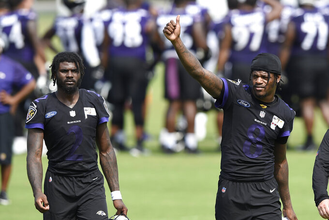 Baltimore Ravens quarterback Lamar Jackson, right, gives a thumbs up after an NFL football practice, Monday, Aug. 9, 2021 in Owings Mills, Md. Also pictured is Tyler Huntley. (AP Photo/Gail Burton)