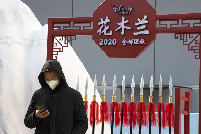 """A man stands in a set promoting the Disney movie Mulan in Beijing on Wednesday, Feb. 19, 2020. Disney is under fire for filming part of its live-action reboot """"Mulan"""" in Xinjiang, the region in China where the government has been accused of human rights abuses against Uighurs and other predominantly Muslim minorities. (AP Photo/Ng Han Guan)"""