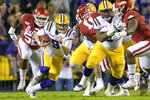 LSU quarterback Joe Burrow (9) is trailed by Arkansas defensive lineman T.J. Smith (52) during the first half of an NCAA college football game in Baton Rouge, La., Saturday, Nov. 23, 2019. (AP Photo/Matthew Hinton)
